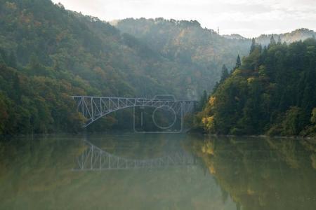 Autumn fall foliage Fukushima First Bridge daiichi kyouryuu from Tadami River bank  in Mishima Fukushima, Japan