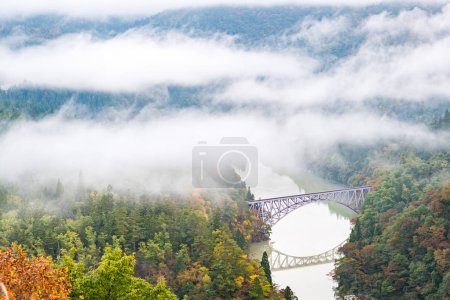 autumn forest and Fukushima First Bridge with Tadami River, Japan