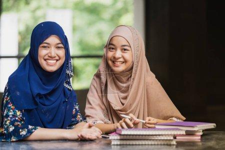 Photo pour Adolescent Jeune adulte asiatique thaïlandais musulman université étudiants lisant le livre et utilisant la tablette numérique ensemble en utilisant pour l'éducation et l'éducation en ligne concept - image libre de droit