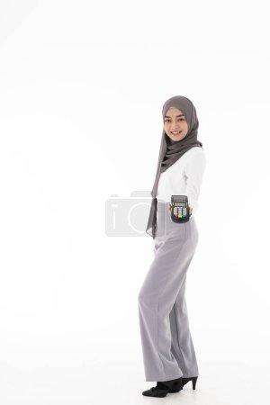 Photo pour Portrait corporel complet d'une femme musulmane souriante et confiante avec une machine EDC comme concept de propriétaire marchand. Studio tourné sur fond blanc. Utilisation à la vente consumérisme et concept shopaholic . - image libre de droit