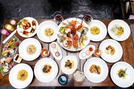Photo for Table top view premium variety of international food in restaurant of lobster shrimp steak beef lamb pasta spaghetti risotto rice sushi sashimi and wine using for buffet food drink background. - Royalty Free Image