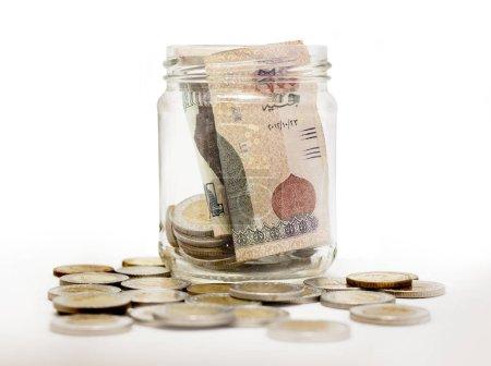 Photo pour Livres égyptiennes, pièces de monnaie et billets en bocal en verre, isolés sur fond blanc - image libre de droit