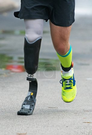 Man running with prosthetic leg on the street.