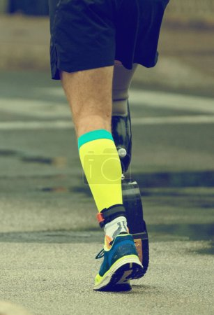 Photo pour Homme qui court avec jambe prothétique dans la rue. - image libre de droit