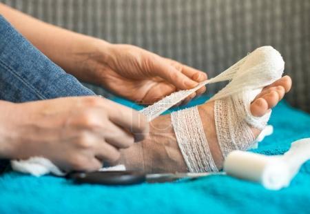 Photo pour Femme bandage sa jambe blessée sur canapé à la maison. - image libre de droit