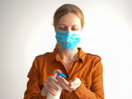 Photo for Protection against coronavirus. masked woman treats hands with antiseptic. - Royalty Free Image