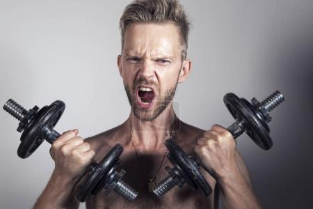 Photo for Man lifting heavy weights and screaming - Royalty Free Image