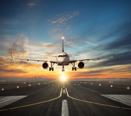 Photo for Passengers airplane landing to airport runway in beautiful sunset light, silhouette of modern city on background - Royalty Free Image