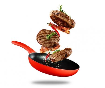 Beef milled meat flying from a pan on white background