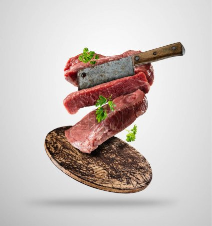 Flying raw steaks with ingredients, food preparation concept