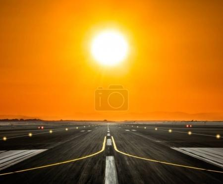 Airport runway with big sun in sunset light