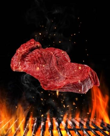 Flying raw steak over grill