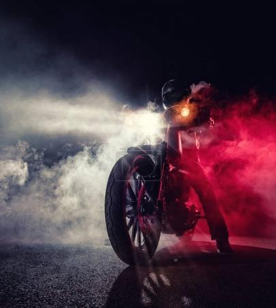 Foto de Chopper de motos de alta potencia con jinete de hombre en la noche. Niebla con luz de fondo en fondo. - Imagen libre de derechos