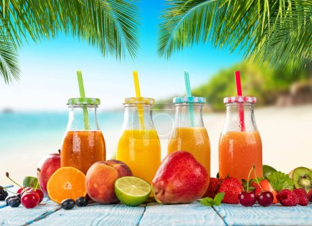 Fresh smoothie drinks placed on wooden planks, blur beach on bac