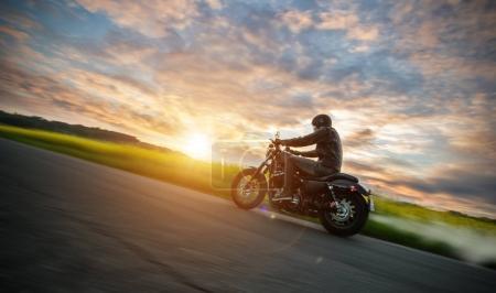 Photo pour Motocycliste sombre chevauchant moto de haute puissance dans la nature avec une belle lumière du coucher du soleil. Voyage et transport. Liberté d'équitation moto - image libre de droit