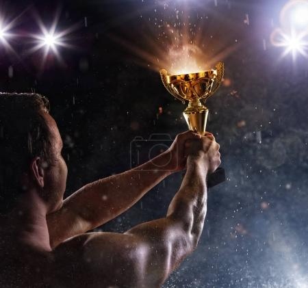 Back view of man fighter with trophy cup in hands, victory gestu