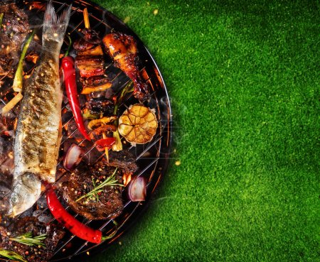 Top view of fresh meat and vegetable on grill placed on grass