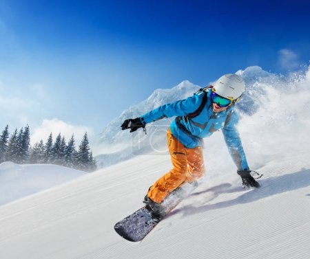 Young man snowboarder running down the slope in Alpine mountains