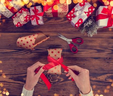 Detail of woman hands packing Christmas gifts