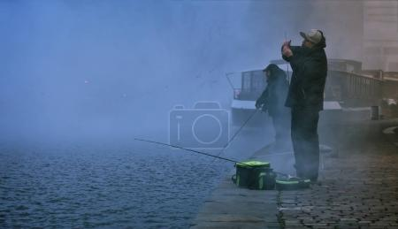 Two fishermen, trying to catch fish in early morning.