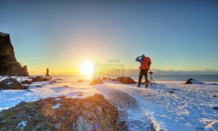 Photo pour Jeune homme voyageur faisant de la photographie, Islande. Concept de liberté et de voyage. Paysage d'hiver, activités de plein air et sport - image libre de droit