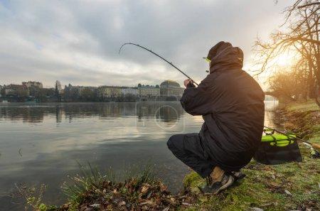Foto de Pesca pescador deportivo tratando de atrapar peces en el río, urbano. Actividades de ocio y Pasatiempos al aire libre - Imagen libre de derechos