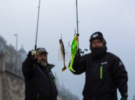 Two sport fishermen showing plastic bait fish.