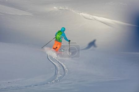 Young freeride skier running downhill in fresh powder snow