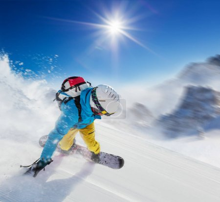 Young man snowboarder running downhill in fast motion