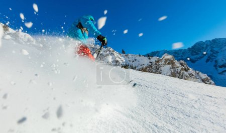 Young man freerider skiing downhill in Alps.