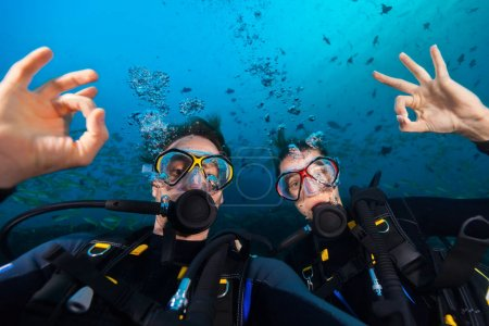 Couple of scuba divers showing ok sign, portrait photography