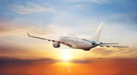 Big commercial airplane flying above clouds in sunset