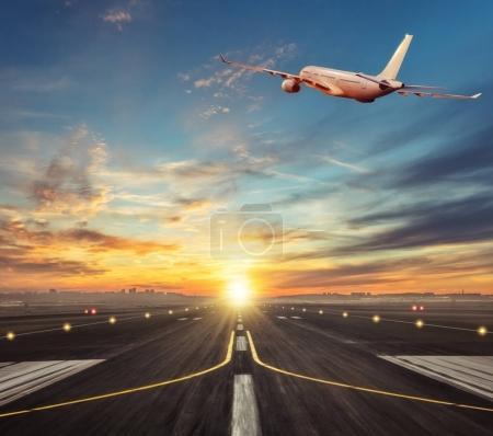 Commercial airplane flying above runway in sunset light.