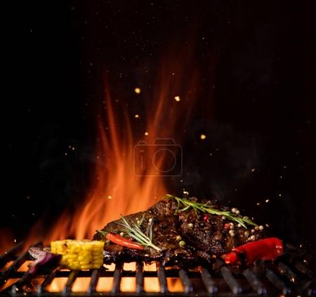 Fiery grill grid with piece of beef steak and grilled vegetable.