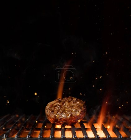 Piece of minced meal for hamburger placed on grill grid.