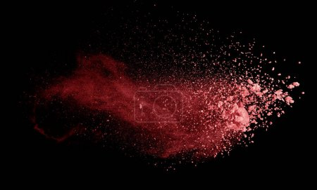 Abstract colored red powder explosion isolated on black backgrou