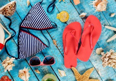 Photo pour Accessoires de plage placés sur des planches en bois bleu, vue de dessus. Concept vacances d'été, espace libre pour le texte. Image à très haute résolution - image libre de droit