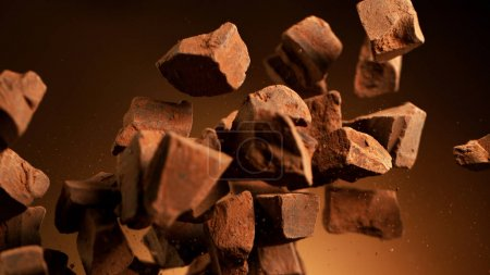 Photo for Flying pieces of crushed chocolate pieces, delicious fresh dark brown chocolate fragments. - Royalty Free Image