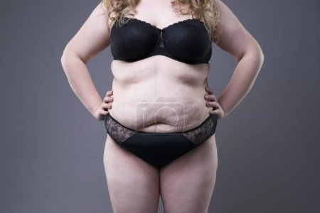 Plus size model in black lingerie, overweight female body, fat woman with stretch marks on gray background