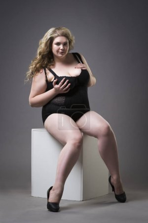 Young beautiful blonde plus size model in shapewear, xxl woman in slimming underwear on gray studio background