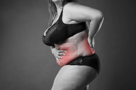Back and abdomen pain, fat woman with backache, overweight female body on gray background