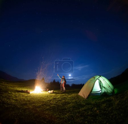 Father and son near campfire and tent under night sky