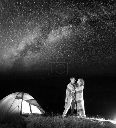 Sweety couple hikers standing together near campfire and tent at night and enjoying starry sky. Pair covered with a plaid. Amazing Milky way. Black and white