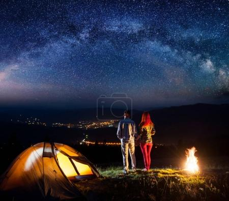 Night camping. Happy couple hikers holding hands