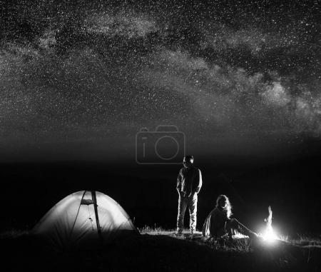 Romantic pair tourists in his camp at night near campfire