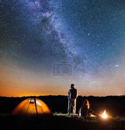 Romantic couple hikers in his camp at night near campfire and tent against starry sky with Milky way