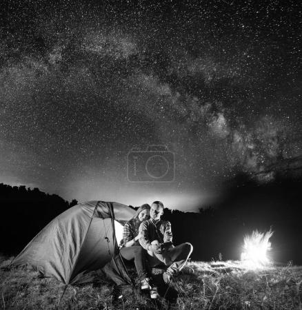 Night camping. Romantic couple sitting in front tent