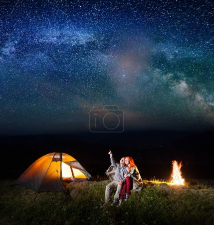 Guy showing red-haired girl at the stars and Milky way