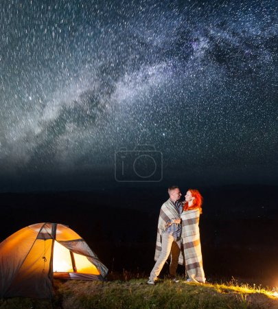 Sweety couple hikers standing together near campfire and tent at night and enjoying starry sky. Pair covered with a plaid. Amazing Milky way