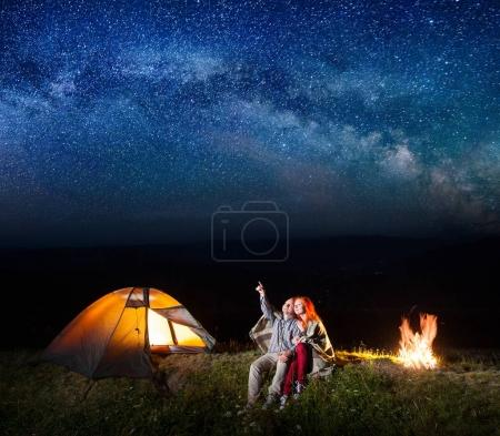 Tourist man showing red-haired woman at the stars in the sky.